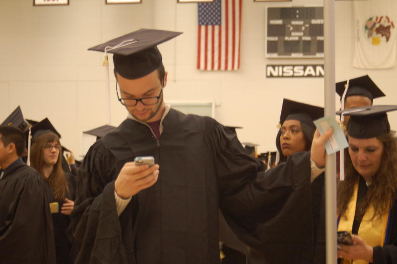 Spanish major Matthew Isaacs checks his phone while standing in line before the NIU College of Liberal Arts and Sciences undergraduate ceremony begins. Isaacs aspires to be a judicial interpretator or a foreign ambassador.