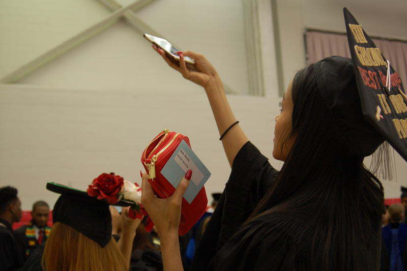 Dana Beverly takes a photo of another graduate's cap while waiting for the undergraduate ceremony to begin Saturday morning.