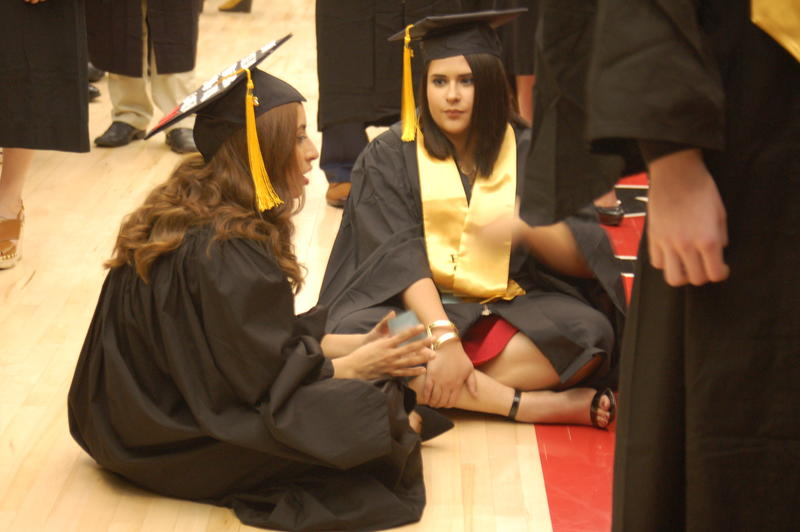 Gabriela Silva (left) and Andra Dobbel (right) sit and wait for the NIU College of Liberal Arts and Sciences undergraduate ceremony to begin Saturday.