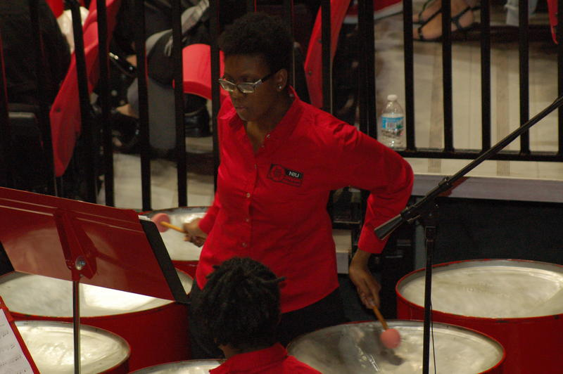 NIU Steel Band member and music student Carla Robinson plays the bass steel pans during Saturday's commencement ceremonies.