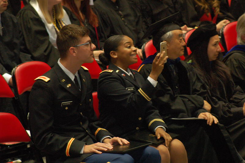 ROTC graduates Walker Steinke (left) and Shanell Walter (right) take a selfie after becoming officers during the NIU undergraduate College of Liberal Arts and Sciences commencement ceremony on Saturday.