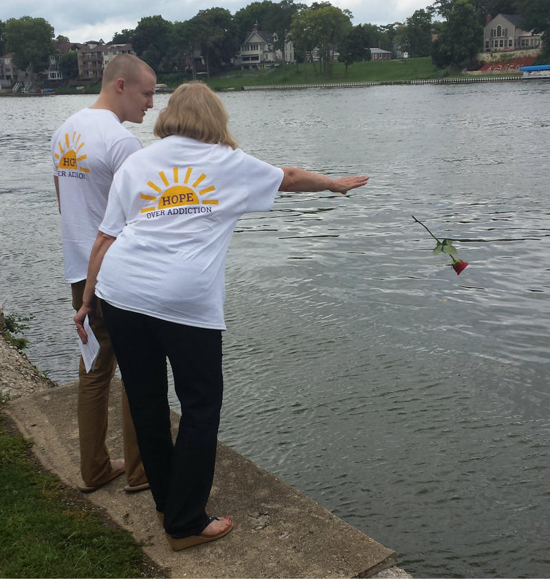 Tammy Wardemann throws a rose into the Rock River to remember a loved one lost to addiction