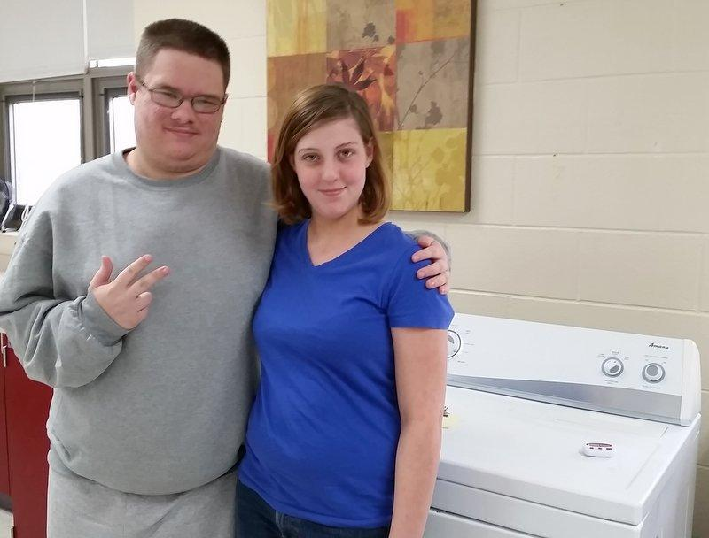 Classmates Hunter James Otto and Kirstin Foulker pose with one of the tools of their classroom trade