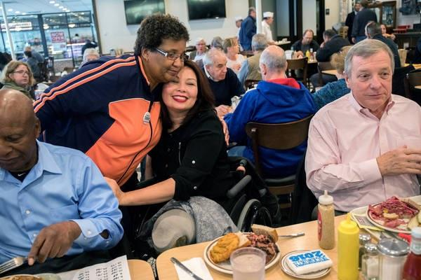Tammy Duckworth (center) candidate for U.S. Senator for Illinois, gets a hug from supporter Demetria Puckett during lunch at Manny's Cafeteria and Delicatessen in Chicago, Ill., earlier today.