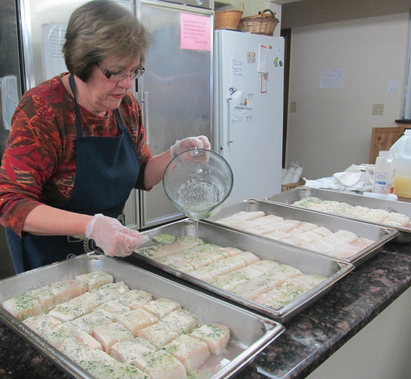 Volunteer Nancy Monachello helps season the cod. The recipe includes wine and garlic. The recipe has been passed down from longtime parishioner Kate Schramer, who is now deceased.