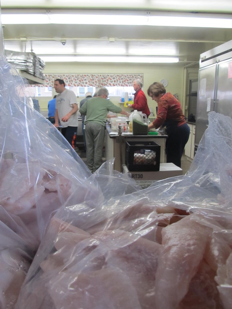 The perch thaws and will be deep-fried in the next few hours. Volunteers have plenty to do between noon-3 p.m. including washing and wrapping potatoes and seasoning the cod