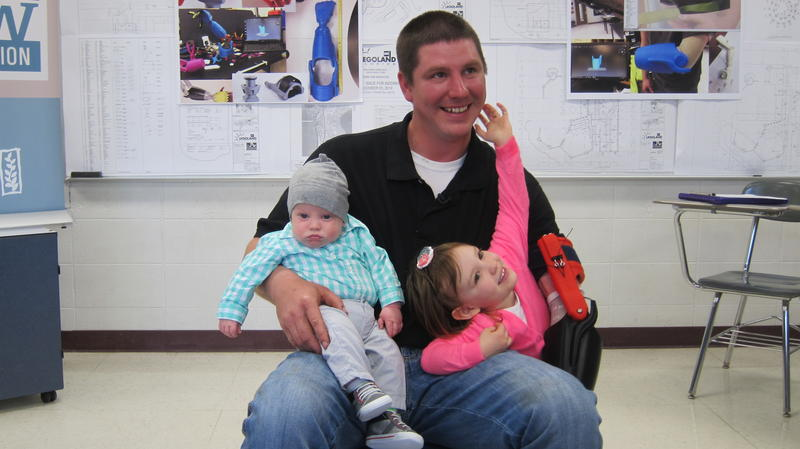 Hubbard sits down with his youngest children and a new arm.