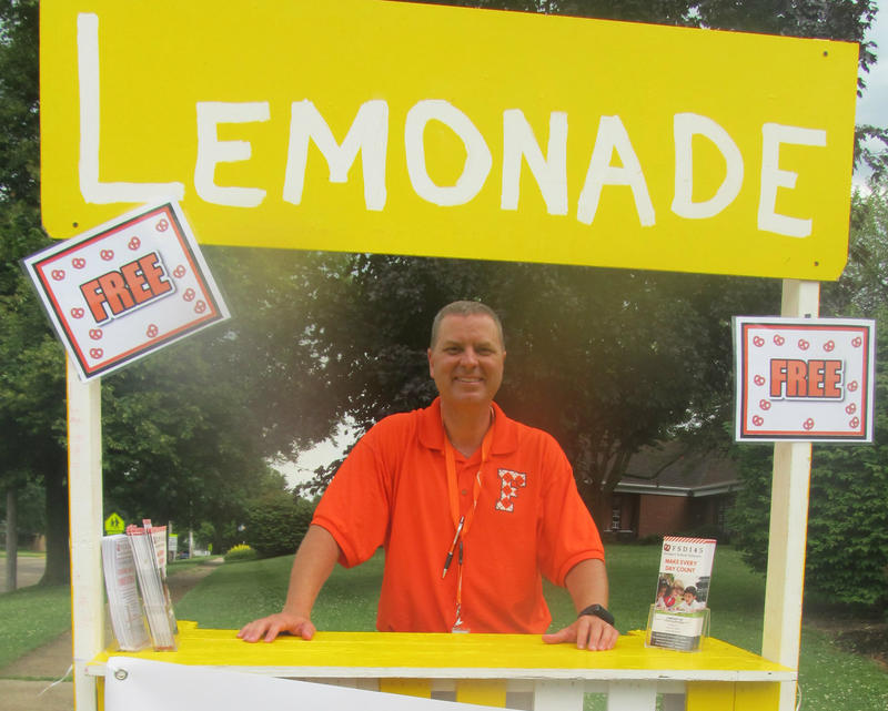 Freeport Superintendent Mike Schiffman hands out lemonade and pretzels on a recent rainy summer day in July.