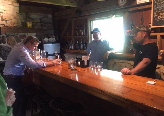 U.S. Rep. Adam Kinzinger samples the newest product as Whiskey Acres CEO Jamie Walter and COO Nick Nagele look on