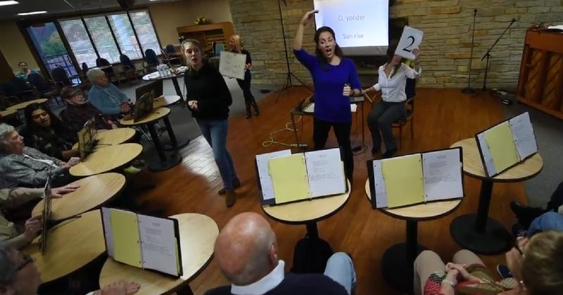 NIU Assoc. Prof. Jamie Mayer, in background with whiteboard, works with graduate student Elizabeth Lanza, center, conducting the Bridges choir at a local nursing home. Singing helps some of the the participants improve their speaking as well.