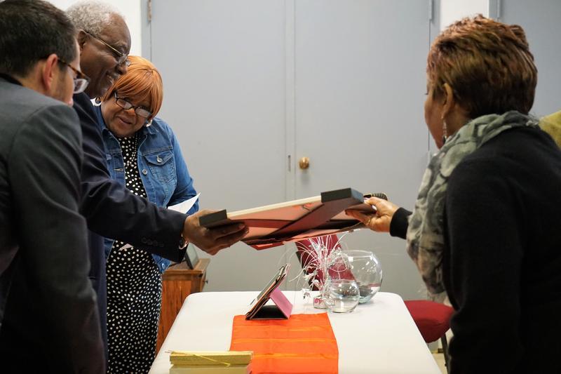 "Estelle Black presents a framed copy of ""The Man From Waco""  to Chuck Jefferson as Mayor Tom McNamara and emcee Joyce Higgins look on."