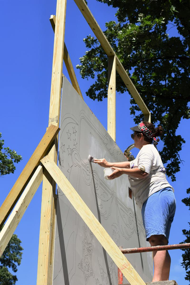 A woman works on a mural in City Park. Murals were to be installed on buildings after paintings were complete.