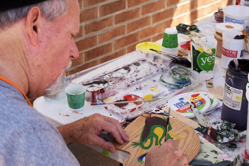 Steve Estes sits at a table and paints at the Streator Walldog Festival. Estes travelled from Clearwater, Flordia to this year's mural fest. He also hosted the second ever Walldog meetup.