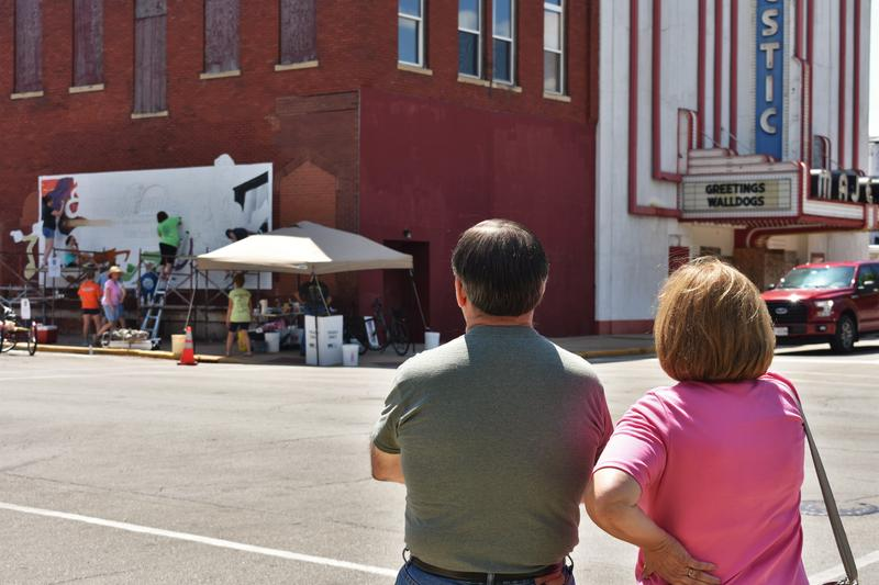 A couple looks on as Walldogs paint a mural on the corner of Vermillion and Hickory Street.