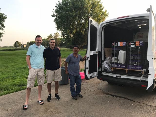 Employees from a Home Depot in Niles unload portable air conditioners it donated to the shelter.