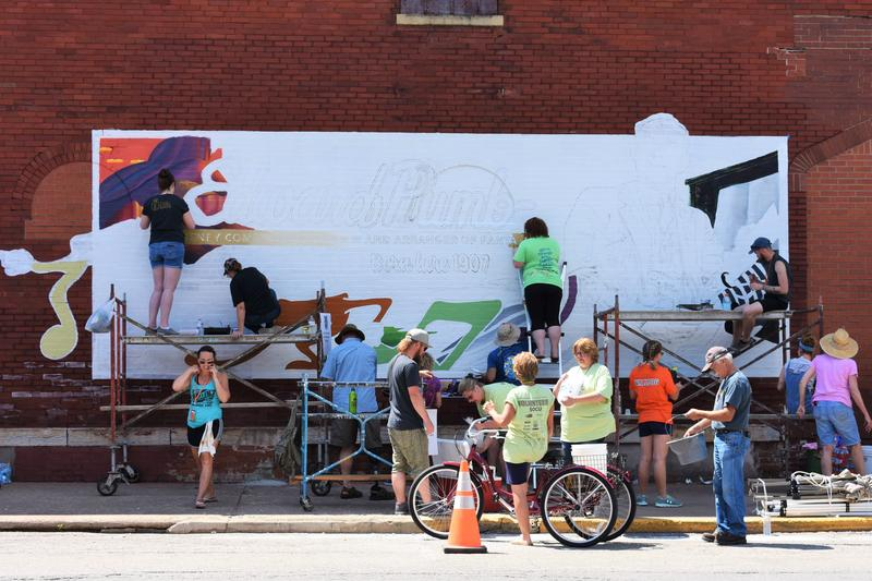 A team works on the Edward Plumb mural. Plumb was born in Streator in 1907. He composed and arranged music for Disney.