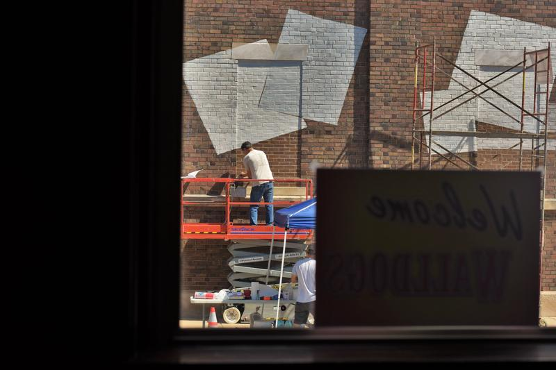 A man works on a mural in Streator, as seen through the window of The Silver Fox, an event venue.