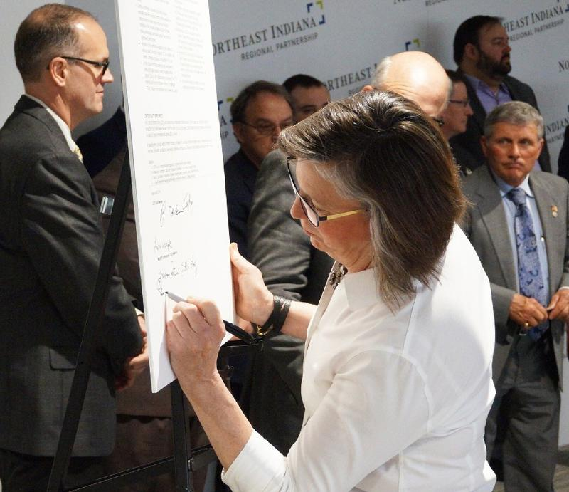 "In a public ceremony, a government official signs the ""code of ethics"" of the Northeast Indiana Regional Partnership as a commitment to a regional approach to economic development."