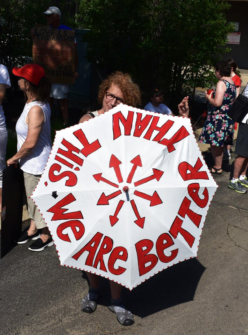 A woman holds up a hand-decorated umbrella that doubled as a sign.