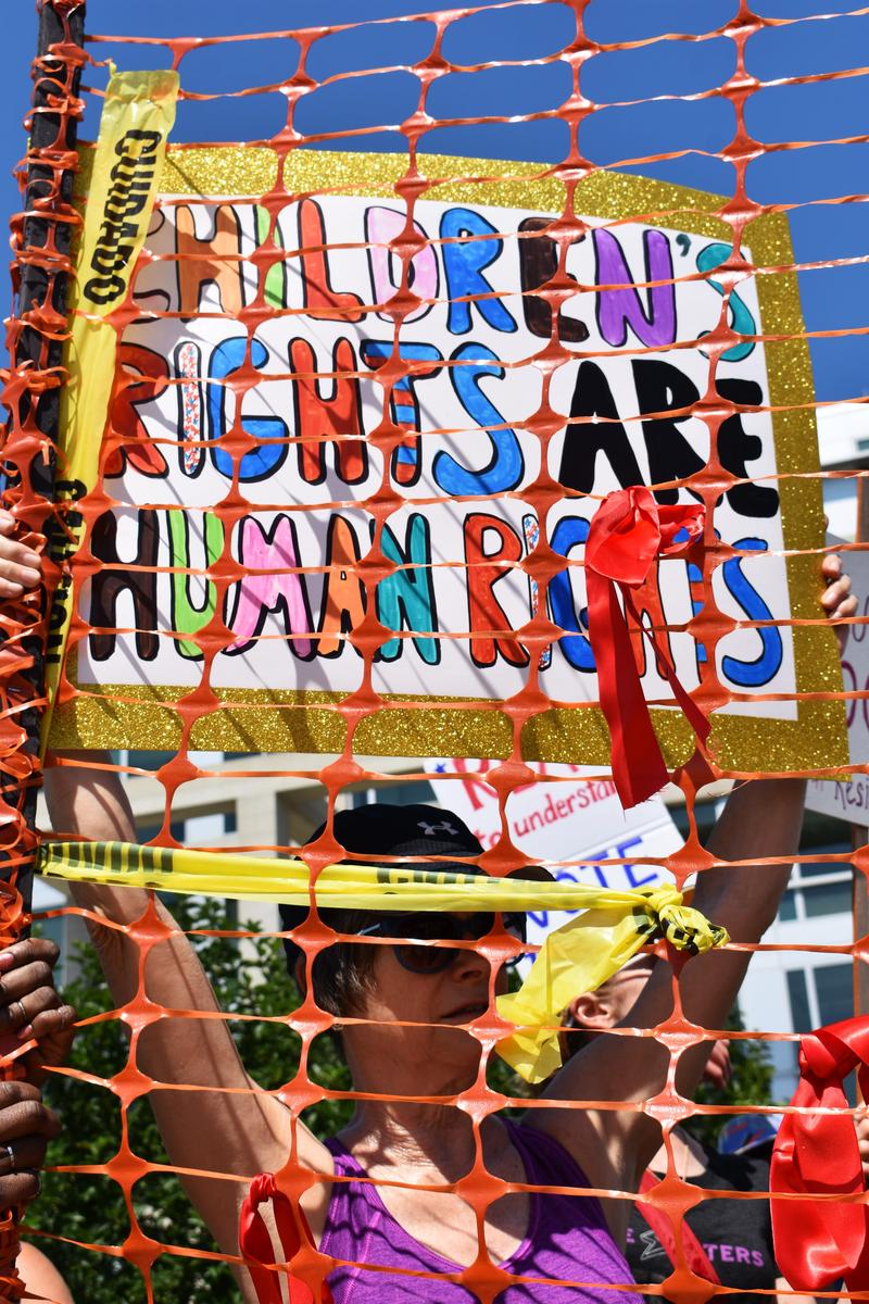 The march ended outside the U.S. Northern Illinois District Court. An orange safty fence used for construction projects was erected. For some, it symbolized the fencing in child detainment centers. For others, it symbolized the southern border.