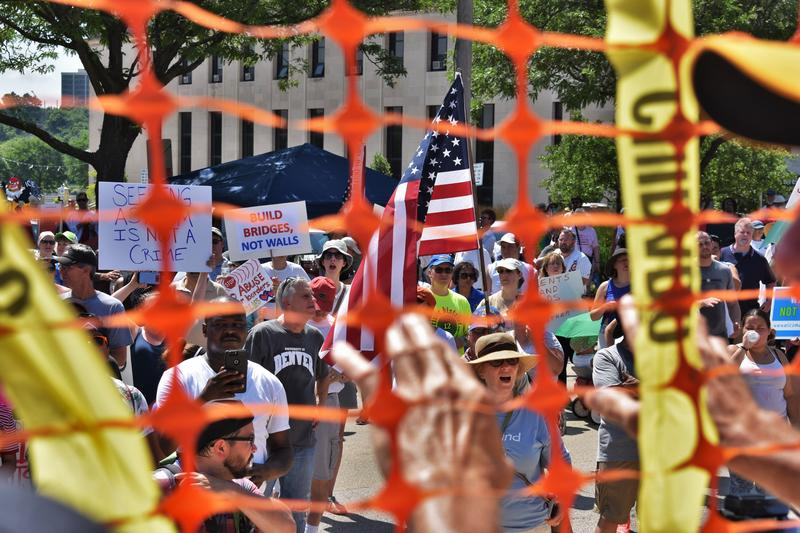 Some demonstrators stood behind the orange fence, facing the crowds of the closing rally.