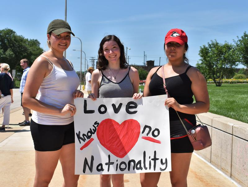 Christina Gomez (left), Isis Hernandez (middle) and Michelle Orozco (right) stand with a sign after the end of the march.