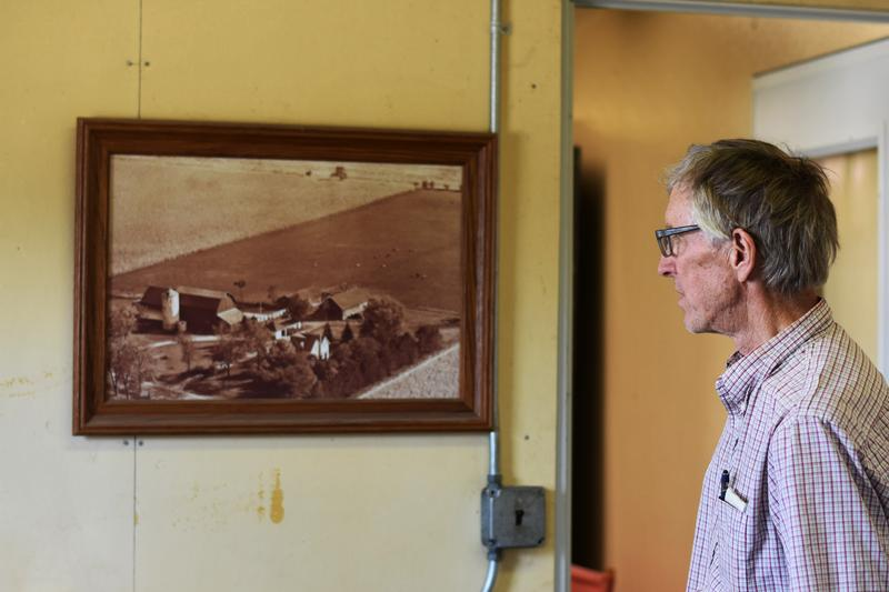 Steve Safford looks at a photo hanging in his farm office. The photo shows what the land looked like when his great grandfather bought the property back in the 1800's.