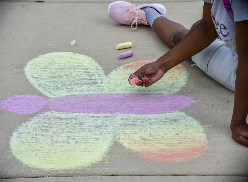 One young lady draws a rainbow butterfly in front of the Rockford Register Star building.