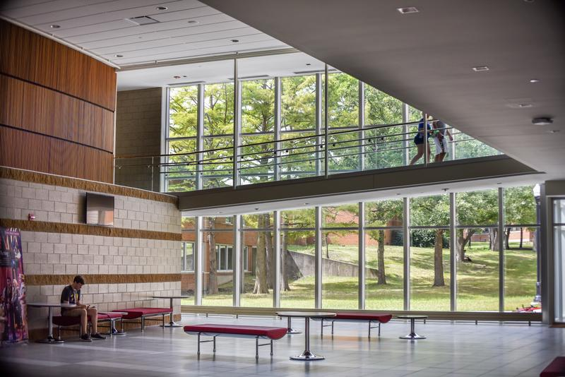 The lobby of the building features glass walkways and a wall of windows.