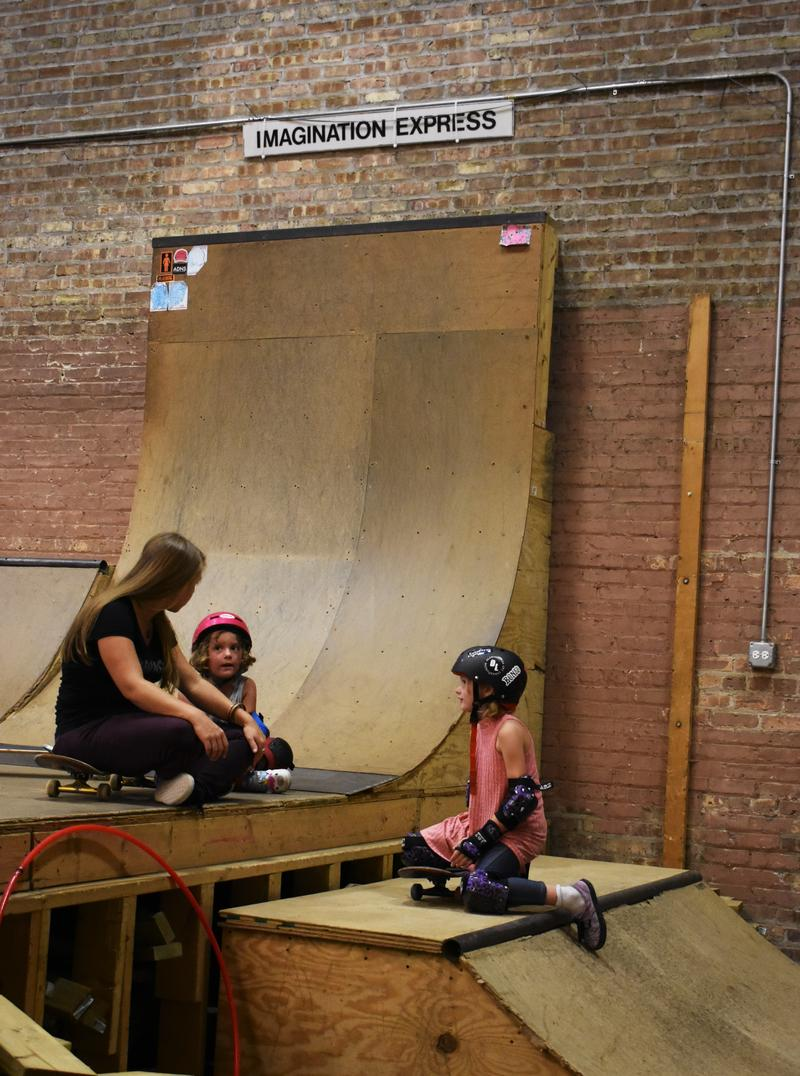 Ariel Ries sits with two of her young skateboarding students. The business hosts a Girls Only session for women who want to learn to skate in a safe environment.