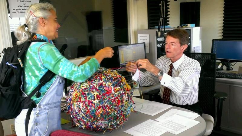 Susan Fowler helps Daniel Moore add smile #12,008 to the yarn ball.