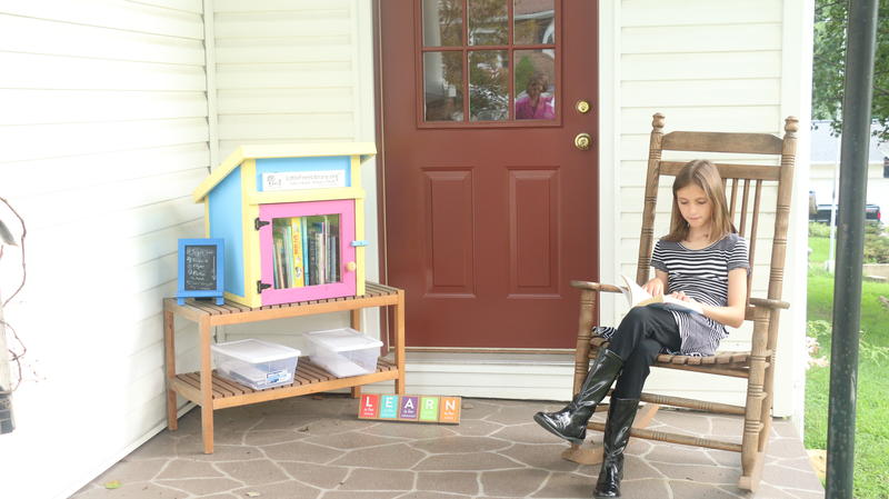 Zoe Smith reads a book from her Little Free Library
