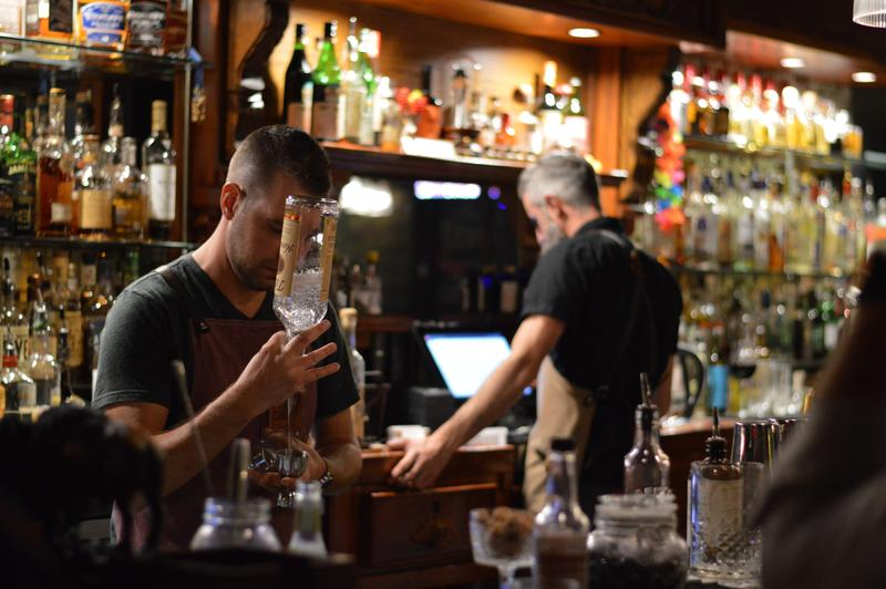 Bartenders at Mo's House tend to customers on a summer evening. At Haynie's Corner, the establishment participates in First Fridays alongside other businesses, artists and organizations.