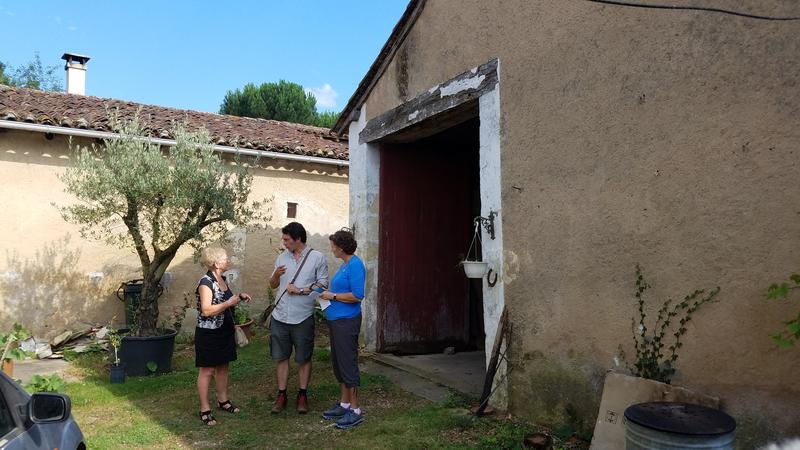 Nancy Hasting (r), chats with Musée André Voulgre director Ludovic Chasseigne and translator Christianne Taildeman at one of the barns in Seguinou that housed U.S. soldiers in World War I
