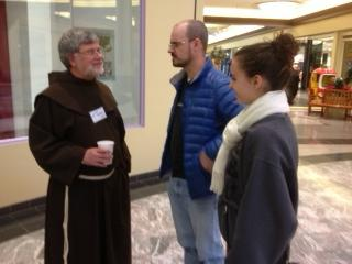 Father Jeffrey Scheeler talks with Dr. Jason Mattingly and his daughter Grace