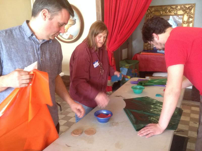 Debbie Von Bokern shows Happen Inc. director Tommy Rueff and Justin Tepe how to make kites
