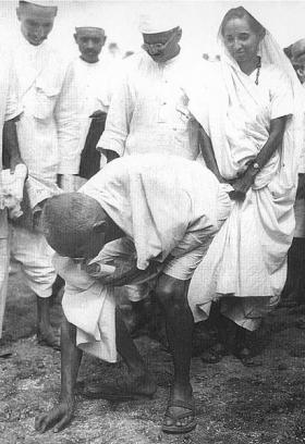 Gandhi at Dandi, South Gujarat, picking salt on the beach at the end of the Salt March, 5 April 1930.