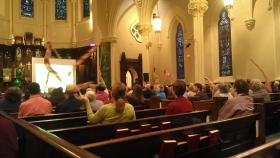 """Participants in a """"Climate Stewardship Summit"""" wave flags during an interfaith worship service at Asylum Hill Congregational Church in Hartford."""