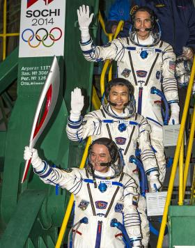 Expedition 38 Soyuz Commander Mikhail Tyurin of Roscosmos, holding the Olympic torch, Flight Engineer Koichi Wakata of the Japan Aerospace Exploration Agency, and, Flight Engineer Rick Mastracchio of NASA top, wave farewell prior to boarding the Soyuz TMA-11M rocket for launch, Thursday, Nov. 7, 2013, at the Baikonur Cosmodrome in Kazakhstan. The Olympic torch has a four-day visit to the International Space Station.