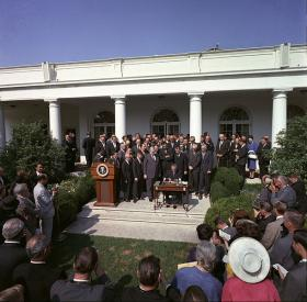 President Lyndon B. Johnson signs the Economic Opportunity Act of 1964.