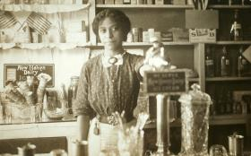 Anna Louise James at the soda fountain where she was pharmacist and owner, Old Saybrook, c. 1909-1911.