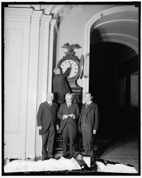 Senate Sergeant at Arms Charles Higgins turns forward the Ohio Clock for the first Daylight Saving Time, while Senators William Calder (NY), William Saulsbury, Jr. (DE), and Joseph T. Robinson (AR) look on, 1918. U.S. Capitol building, Washington, D.C.