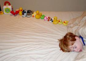 A young boy with autism with a line of toys he sorted before falling asleep.