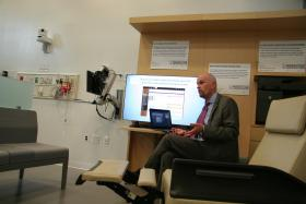 Another major change is the use of a reclining chair instead of a fixed exam table, a large screen so patients can see what a doctor is typing, and a chair where the doctor sits at the same level as the patient.