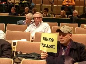 "A resident holds up a ""Trees Please"" sign during a public hearing on ""enhanced tree-trimming"" in March."