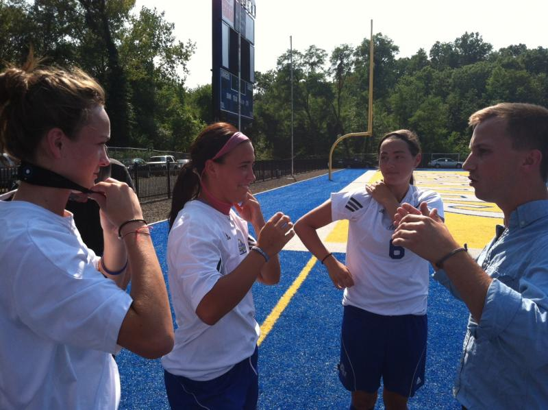 Members of the UNH soccer team are shown how to wear the sensor headbands