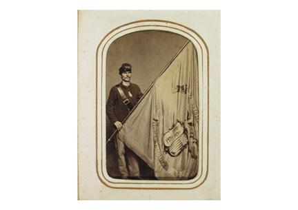 Corporal Thomas Fox, Co. B, Second Connecticut Heavy Artillery. Photograph by Beers & Mansfield, New Haven, 1864.. Fox holds the Second's regimental flag. Though the unit originally consisted primarily of Litchfield County men, Fox hailed from Norwich.