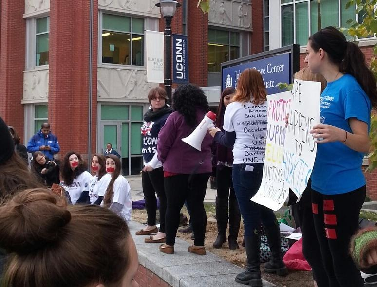 Alexandra Katz, at far right, holds a sign in support of seven women who filed a federal discrimination complaint against UConn. Seated are Erica Daniels, Carolyn Luby, and Rose Richi.