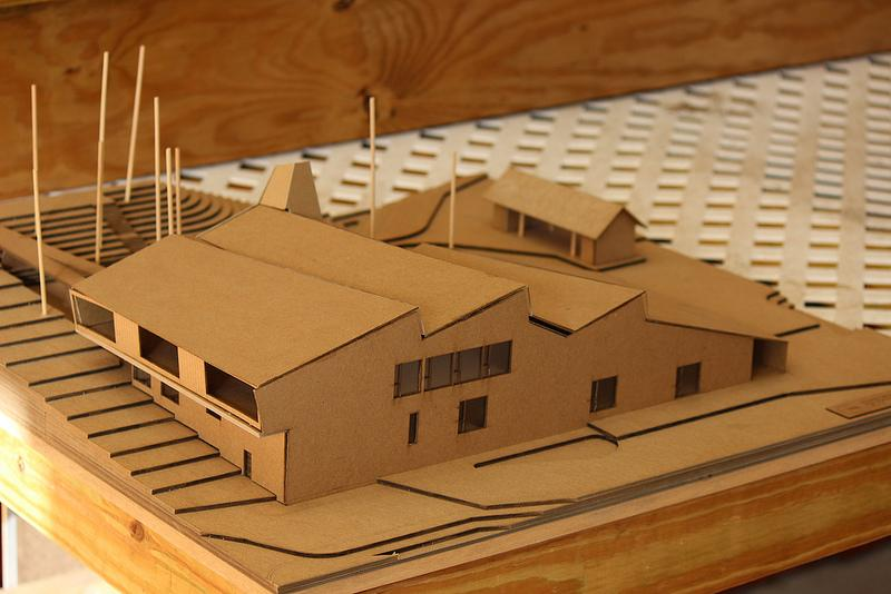 A model of the new building shows additions to the campus, including two science labs, an art studio, and a community gathering and performance space.