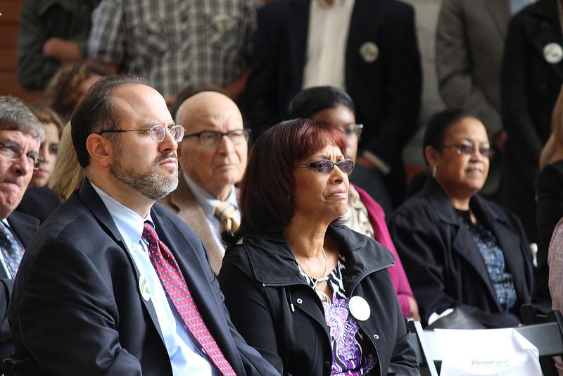 Education Commissioner Stefan Pryor listened to speakers alongside State Rep. Toni Walker.